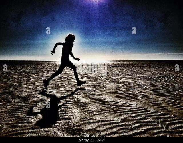 Girl running on empty beach in silhouette - Stock Image