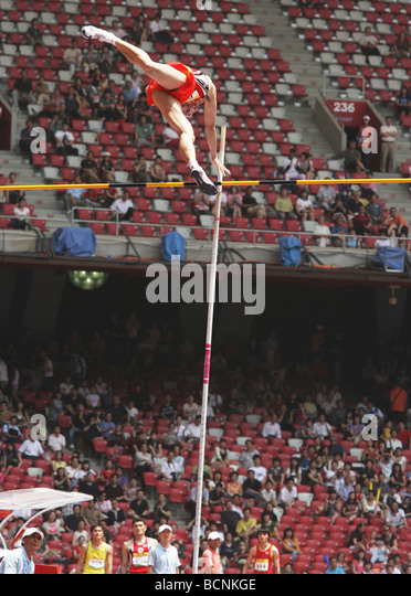 Male athelete flying over mark during Pole Vault competition, Beijing, China - Stock Image