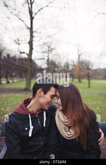 Teenage couple sitting on a bench and enjoying a day in the park. Beautiful young couple in park. Mixed race male - Stock Image