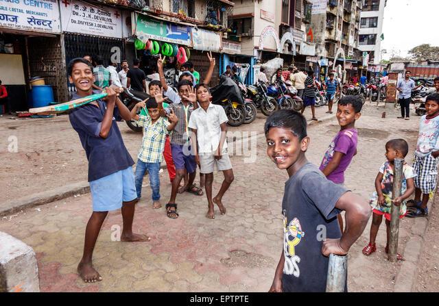 Mumbai India Asian Dharavi 60 Feet Road slum low income poor poverty boy friends playing cricket bat - Stock Image