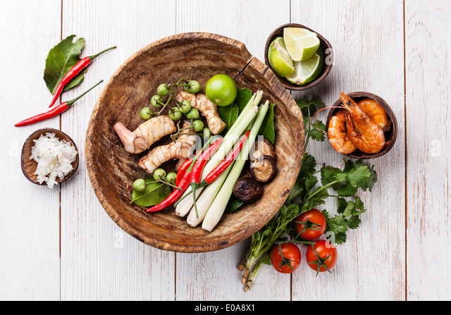 Ingredients for spicy Thai soup Tom Yam with Coconut milk, Chili pepper and Seafood on white wooden background - Stock Image