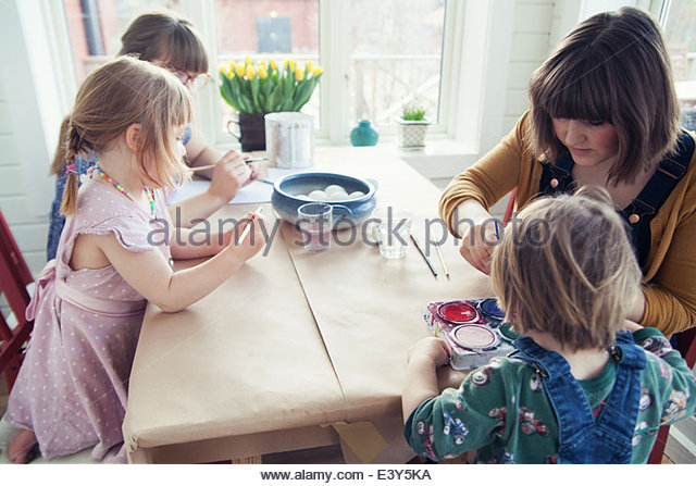 Family painting easter eggs at table - Stock Image