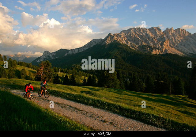 Female mountain bikers cycling through Karer Pass, Mt. Latemar in the background, Dolomites, Northern Italy, Europe - Stock Image