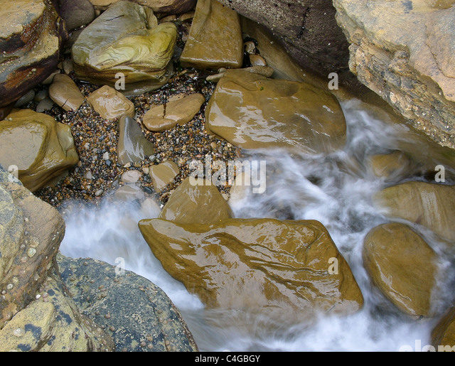 Waves rush into a rock gully at the coast - Stock Image