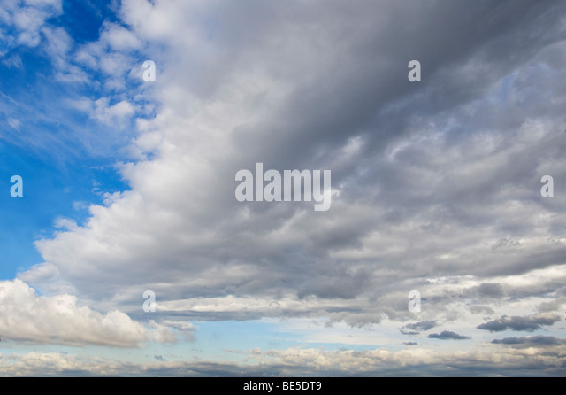blue sky with large white/grey clouds front - Stock Image