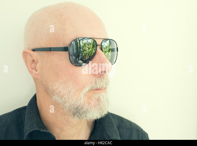 Old man with cool sunglasses looking away. Green garden reflected in the glasses. - Stock-Bilder