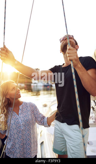 Man Checking Boat While Woman Looking, Warm Summer Day - Stock Image