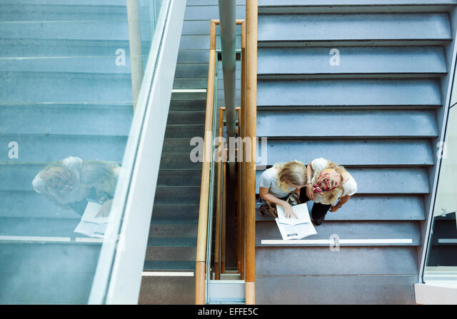 High angle view of students reading book on steps in college - Stock Image