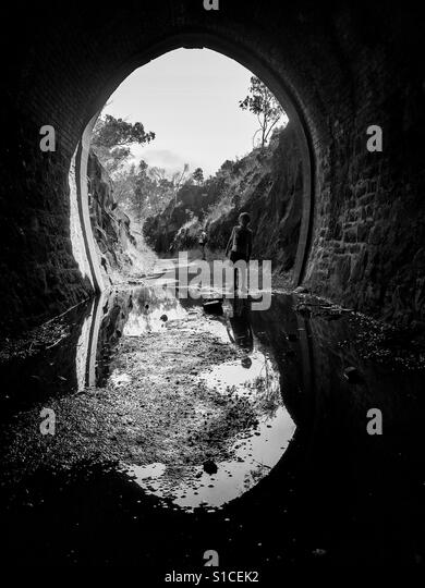 Boy in entrance to tunnel, reflection in water - Stock-Bilder