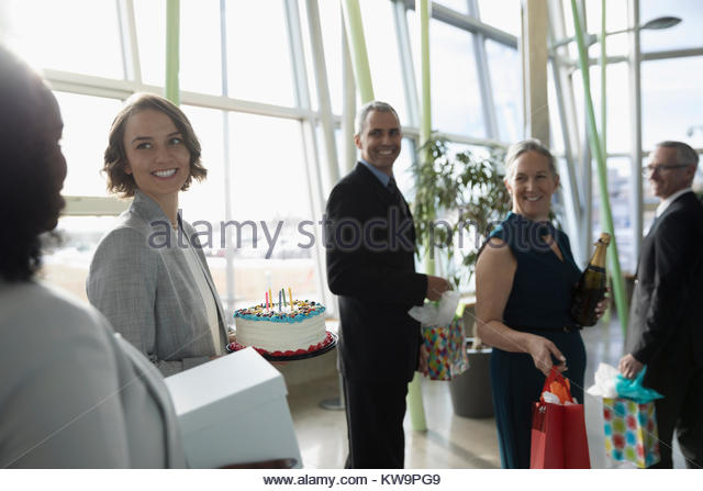 Happy business people carrying birthday cake and gifts in office - Stock Image