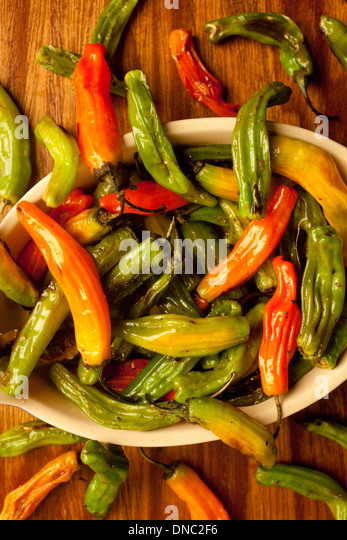 green and orange roasted peppers on white plate overhead - Stock Image