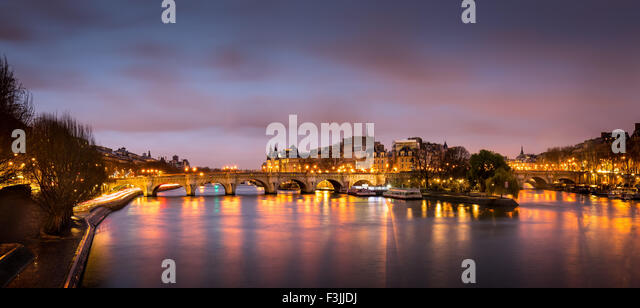 Sunrise in the heart of Paris, France with Ile de la Cite and Pont Neuf. A calm Seine River reflects the city lights. - Stock Image