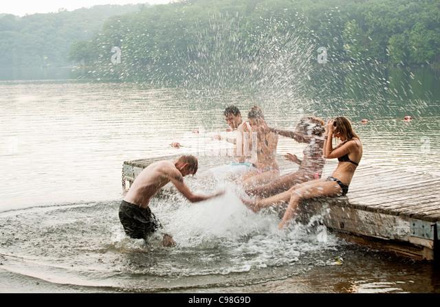 Mid adult man splashing friends lake - Stock Image