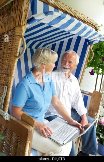 Retired couple using laptop on garden seat - Stock-Bilder