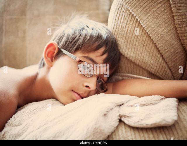 Boy lies on sofa early morning. - Stock Image