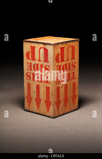 Wooden crate on warehouse floor, upside-down. - Stock Image