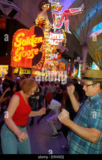 Nevada Las Vegas Downtown Fremont Street Experience pedestrian mall night nightlife neon signs man woman dancing - Stock Image