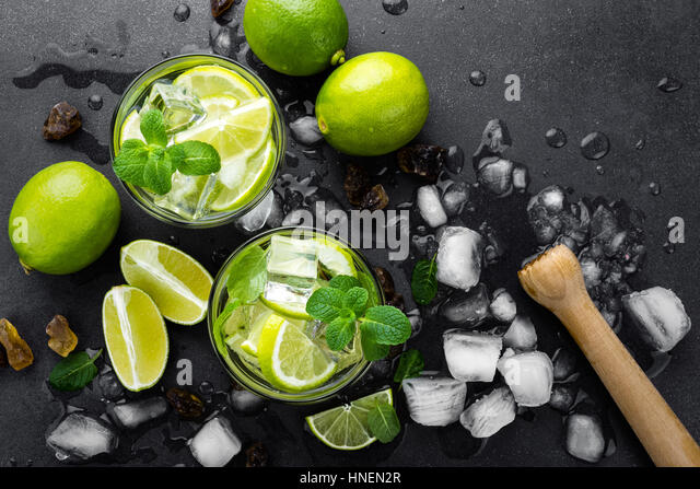Summer mint lime refreshing cocktail mojito with rum and ice in glass on black background top view - Stock Image