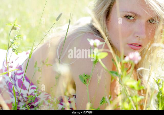 MODEL RELEASED. Young woman lying in meadow with wild flowers. - Stock-Bilder