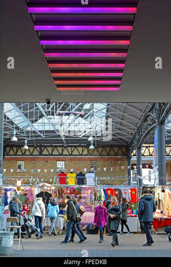 Vary coloured lighting panels above wide access corridor into part of The Old Spitalfields covered market in London - Stock-Bilder