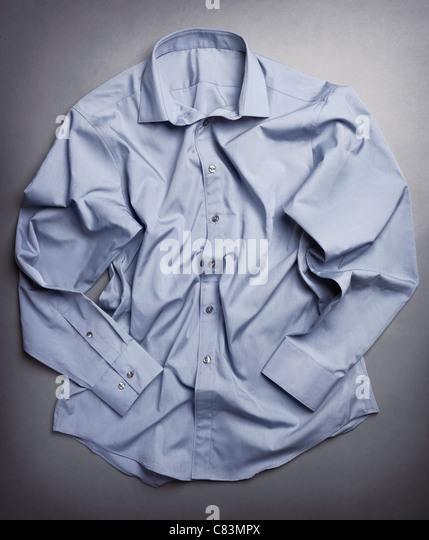 Photo of artistically crumpled mens dress shirt on gray background - Stock-Bilder