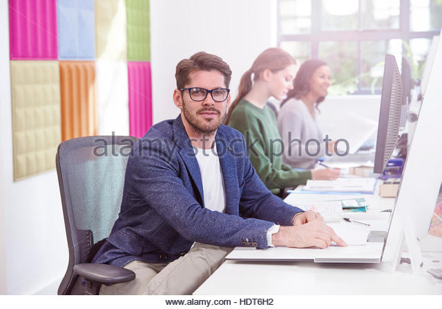 Mid adult businessman sitting at his desk. - Stock Image