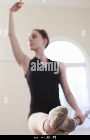 Teenage ballerina dancing at the barre in ballet school - Stock Image