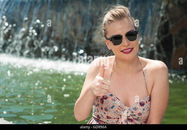 Attractive lady wearing shades showing thumb up gesture with waterfall background and copy text space - Stock Image