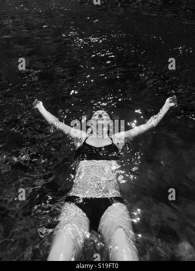 A young woman floats in a pool. - Stock Image