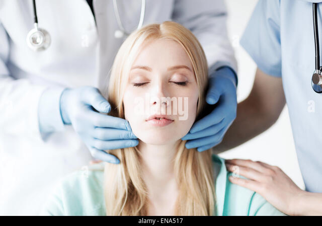 plastic surgeon or doctor with patient - Stock Image
