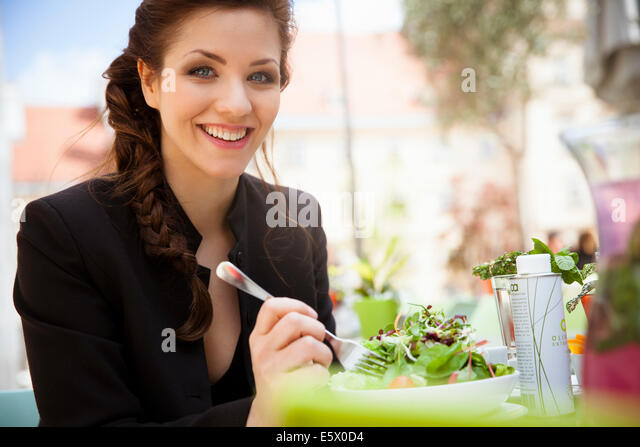 Young adult woman eating salad, outside - Stock Image