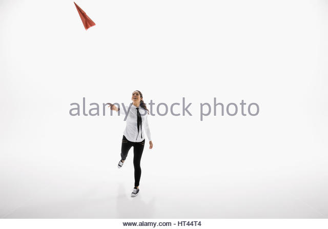 Businesswoman throwing paper airplane against white background - Stock-Bilder