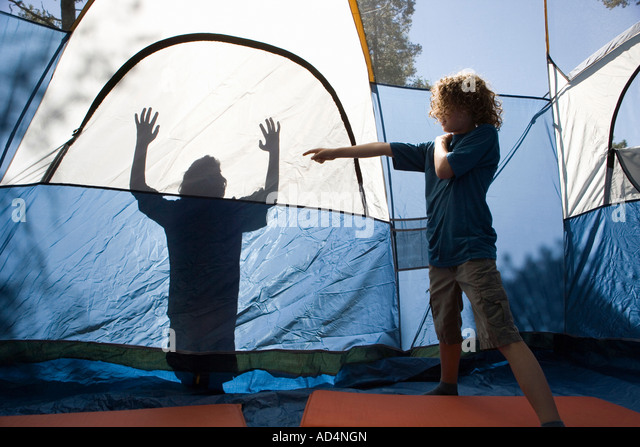 A young boy pointing to a shadow on a tent - Stock-Bilder