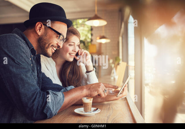 Smiling young couple in a coffee shop using touch screen computer. Young man and woman in a restaurant looking at - Stock Image