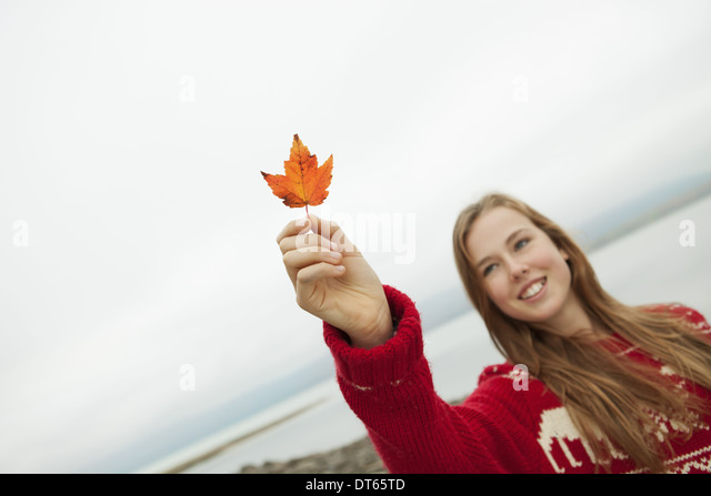 A day out at Ashokan lake. A young girl in a red winter knitted jumper holding up a maple leaf. - Stock Image