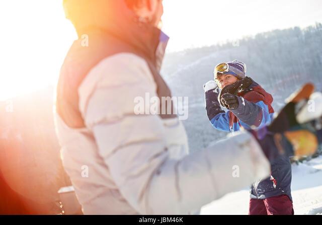 Friends enjoying snowball fight in sunny, snowy field - Stock-Bilder
