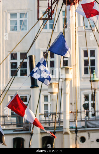Colorful flags on old sailing boat in Nyhavn in Copenhagen. Denmark - Stock Image
