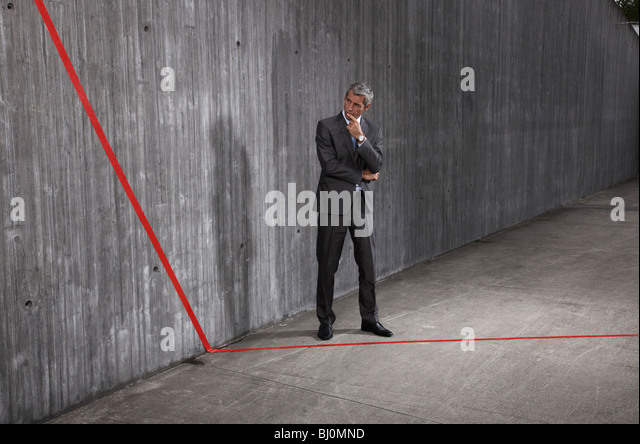 businessman looking at red line - Stock Image
