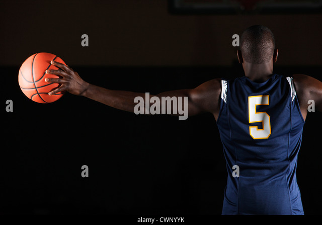 Basketball player holding basketball in hand, rear view - Stock Image