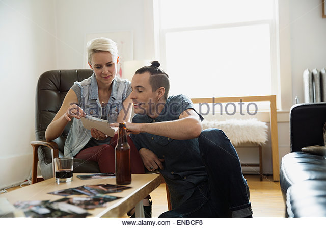 Couple looking at photographs in living room - Stock-Bilder
