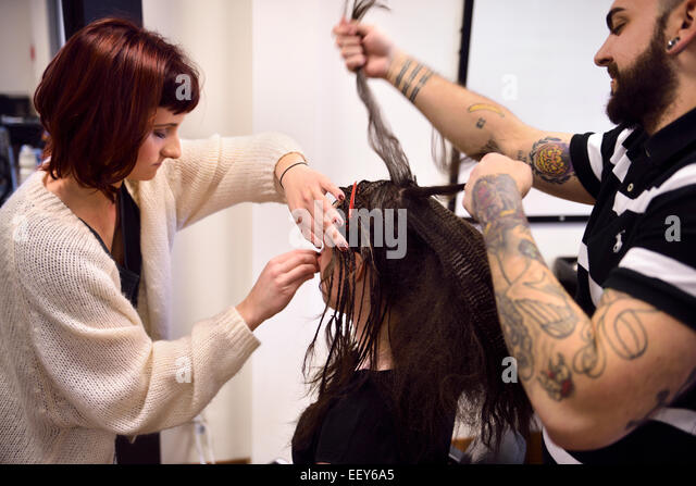 Student hairstylist and makeup artist working on hair and face of a model in a salon - Stock Image