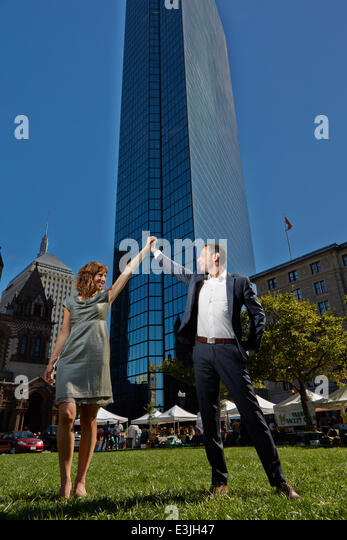 Couple Holding Hands  in front of John Hancock Tower, Copley Square, Boston, USA - Stock Image