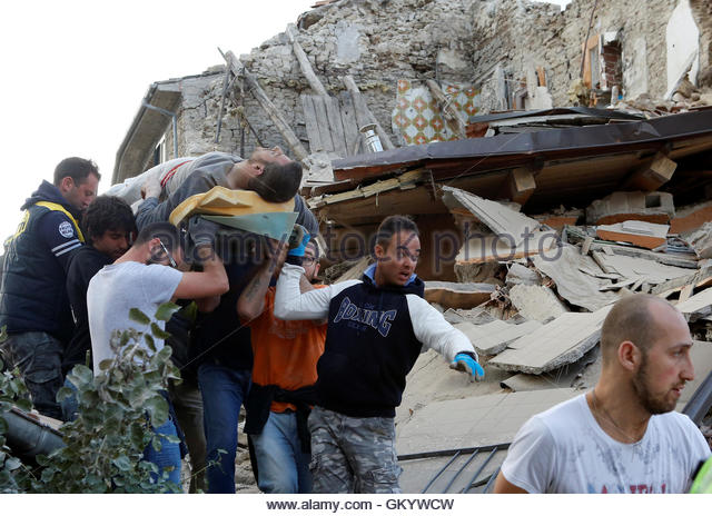 A man is carried away after having been rescued alive from the ruins following an earthquake in Amatrice, central - Stock-Bilder