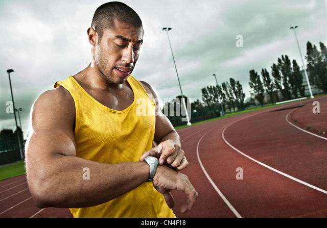 Sprinter looking at watch on race track - Stock Image