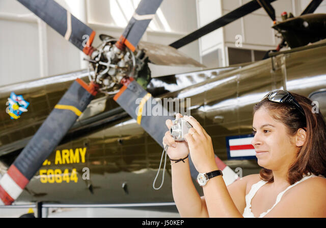 Alabama Ft. Fort Rucker United States Army Aviation Museum Hispanic woman camera memory aircraft military helicopters - Stock Image