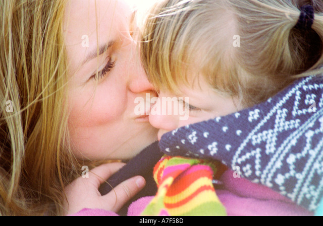 Mother kissing her daughter whilst in embrace - Stock-Bilder