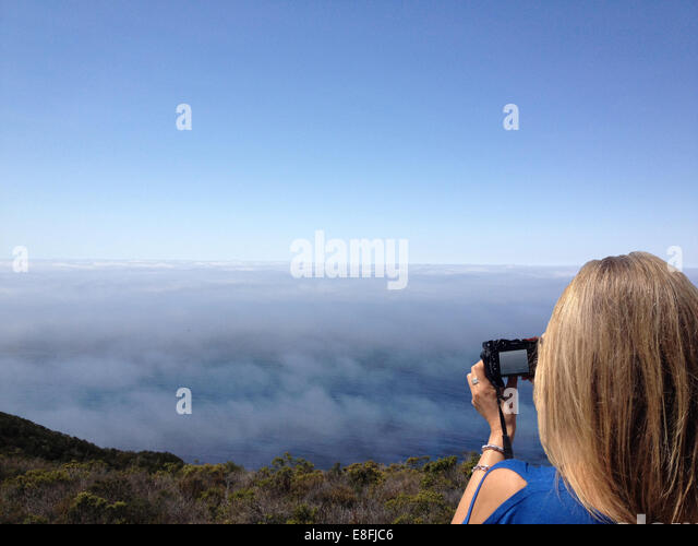 USA, California, Monterey County, Big Sur, Young woman taking photo from California State Route 1 - Stock Image