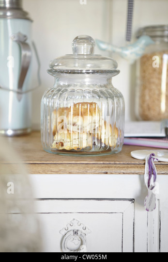 Glass jar of scones on counter - Stock Image