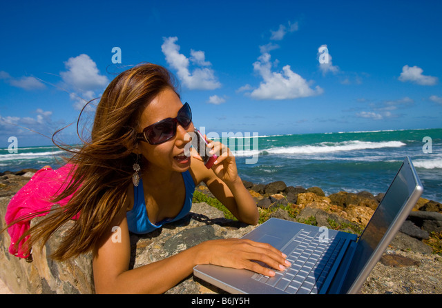 Young Asian woman using a laptop at the beach while she's talking on a cell phone, San Juan, Puerto Rico - Stock Image