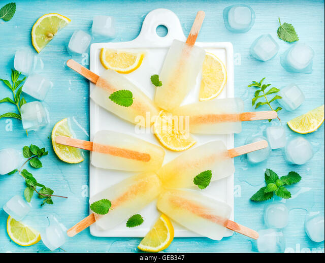 Lemonade popsicles with lemon slices, fresh mint leaves and ice cubes on white ceramic board - Stock Image